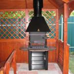 стальной металлический мангал установлен в деревянную беседку